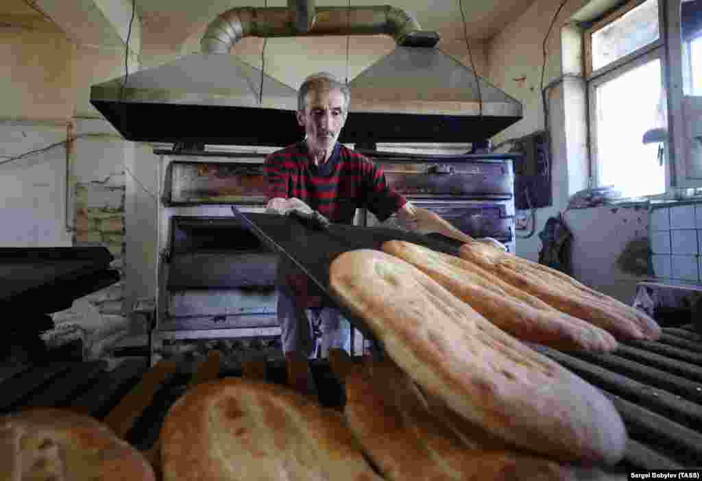 On October 9, 2020, the day talks began in Moscow on a ceasefire between Armenian and Azerbaijani forces, a man in the main Karabakhi town of Stepanakert (Khankendi) bakes bread. The breakaway region receives most of its foodstuffs from Armenia. Its agricultural sector was largely destroyed during Armenia and Karabakhi separatists' 1992-1994 war with Azerbaijan.