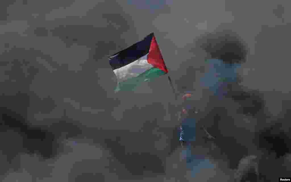 Палестинец в дыму от горящих покрышек протестует против переноса американского посольства в Иерусалим