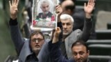 IRAN -- Iranian lawmakers holding pictures of slain Iran's Quds Force leader Qasem Soleimani as they chant 'death to America', during a parliament session in Tehran, January 7, 2020