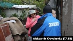 Сотрудник миссии ОБСЕ помогает раненой девушке, пострадавшей после обстрела в Донецке. 10 мая 2017 года