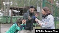 Using a digital translator on his smartphone, Iranian migrant Amir Chani talks with Current Time Riga correspondent Marija Andrejeva at Latvia's Mucenieki migrant detention center.