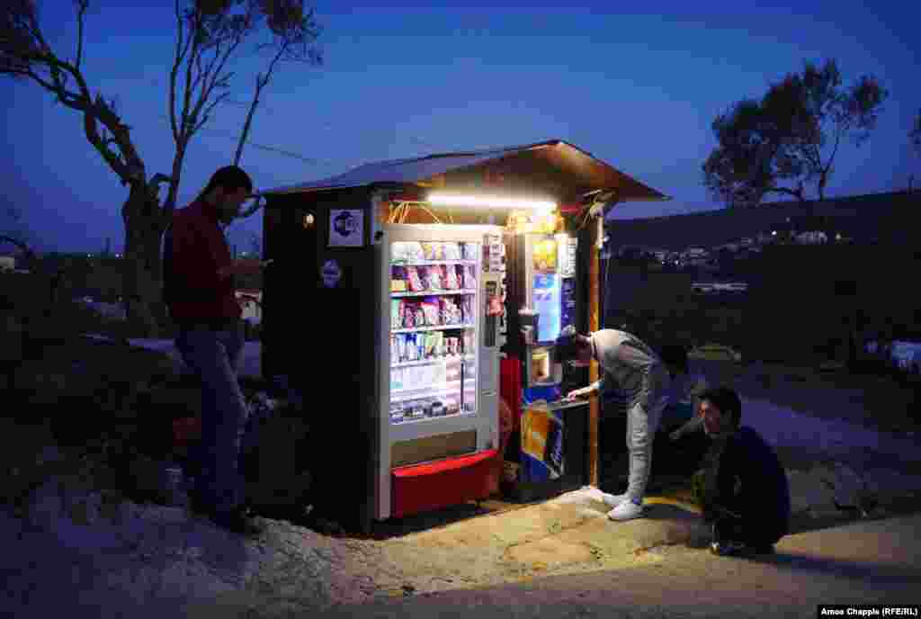 Вечер в лагере, его обитатели заряжают телефоны. На заднем планы видны огни деревни Мориа