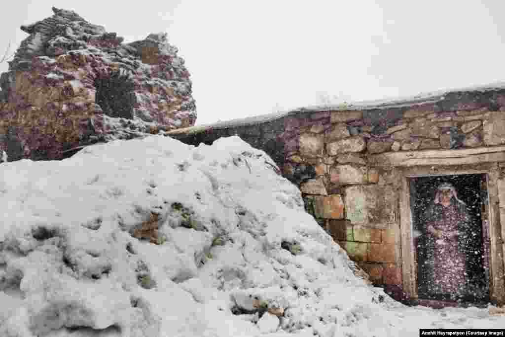 Эта женщина стоит рядом с тандыром, построенным из развалин церкви