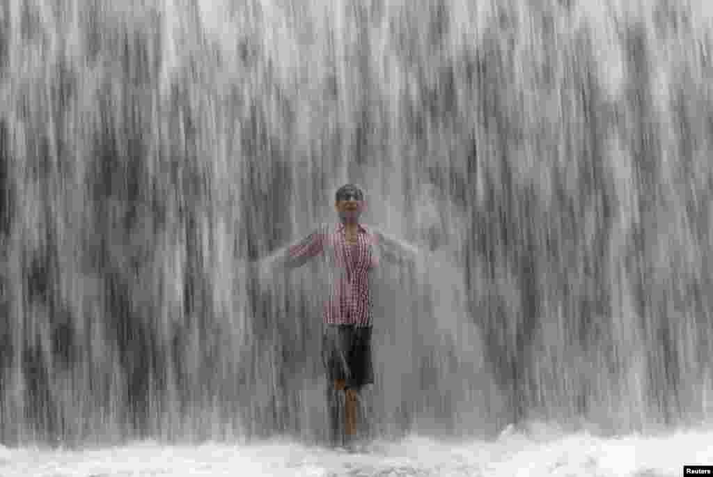 Мальчик стоит у плотины возле озера Повай, переполненной после сильных дождей в Мумбае (Reuters/Shailesh Andrade)