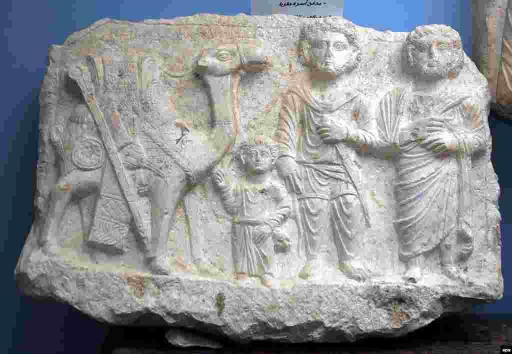 Этот барельеф тоже был найден во время раскопок в 2008 году. На нем изображены пальмирские купцы, ребенок и верблюд