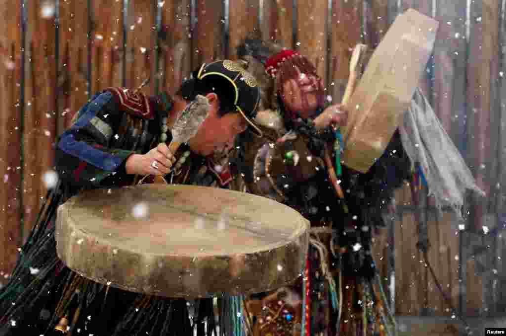 """Бубен – важный шаманский атрибут. Считается, что именно он помагает шаману перенестись в мир духов и обратно. Чем громче и чаще удары, тем быстрее шаман продвигается в загробном мире. Бубен шаманы также называют """"конем"""" На фото – шаманы общества """"Медвежьего духа"""" проводят ритуал"""