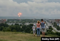 A family watches explosions at a military ammunition depot near the city of Achinsk in eastern Siberia's Krasnoyarsk region on August 5, 2019.