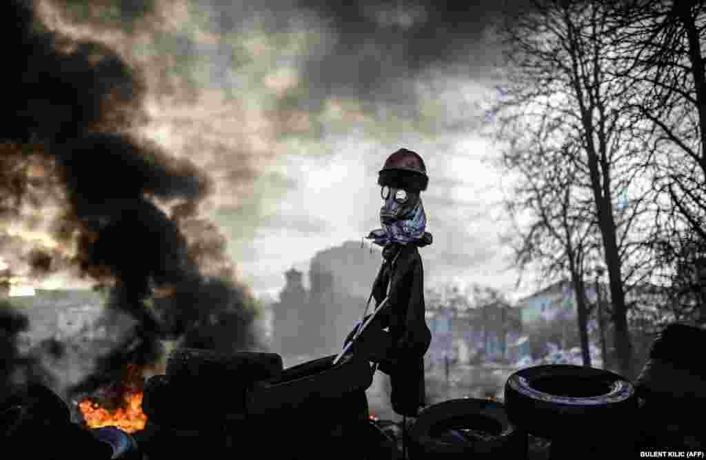 Фигура, похожая на чучело, стоит на баррикадах в Киеве. После ожеточенных столкновений сторонников евроинтеграции с правительственными силами президент Украины Виктор Янукович был вынужден покинуть столицу, после чего парламент лишил его полномочий. 21 февраля.(Bulent Kilic, AFP)