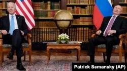With a globe of the world in the background, U.S. President Joe Biden and Russian President Vladimir Putin meet for their June 16, 2021 summit at Villa La Grange in Geneva.