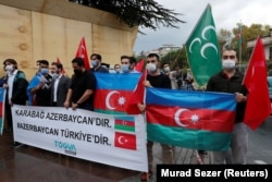 "Turkish men in Istanbul hold a banner that reads ""Karabakh is Azerbaijan. Azerbaijan is Turkey."" during a September 29, 2020 protest against Armenia."