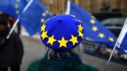 EU flag -themed beret while waving EU flags