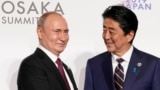 Osaka, Japan - Russia's President Vladimir Putin and Japan's Prime Minister Shinzo Abe / Russia's President Vladimir Putin is greeted by Japan's Prime Minister Shinzo Abe at the G20 leaders summit in Osaka, Japan, June 28, 2019. REUTERS/Kevin Lamarque