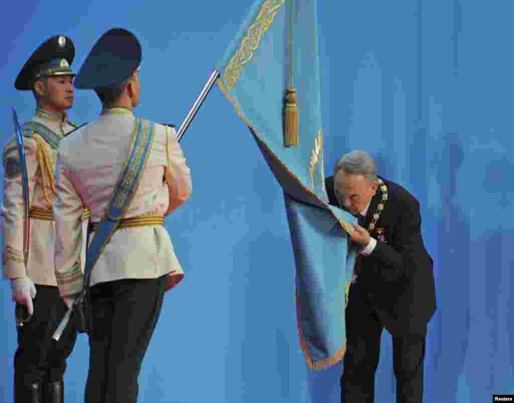 Президент Казахстана Нурсултан Назарбаев целует государственный флаг после принесения присяги. Астана, 8 апреля 2011 года.