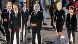 UKRAINE – People look on cutouts depicting Ukrainian presidential candidates, Russian President Vladimir Putin (2L) and Ukrainian businessman Ihor Kolomoyskyi (C) during a performance of activists, in Kyiv, 28 March 2019