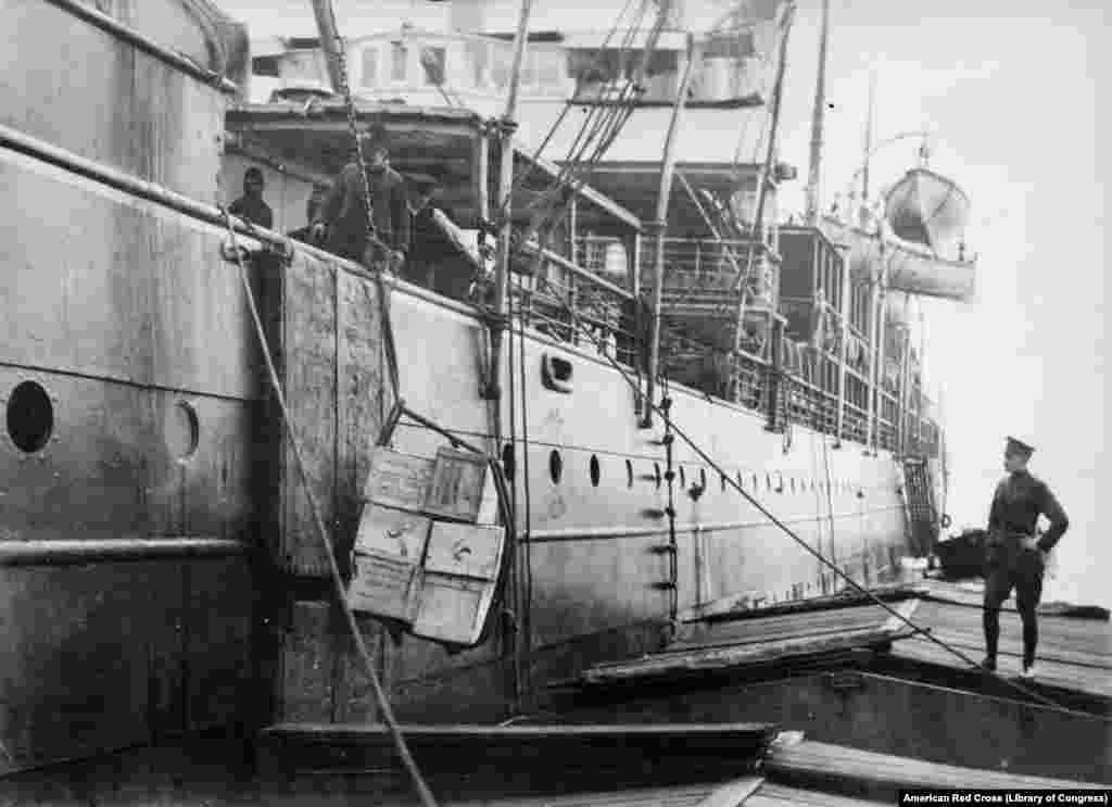 """""""Американскую еду для россиян"""" загружают на судно в Гамбурге. На 50 тысячах упаковок концентрированного молока, которые были посланы в Россию вскоре после революции 1917 года, было написано: """"Свободной России от свободной Америки"""""""