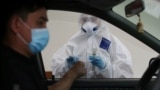 Almaty, Kazakhstan - A health worker approaches a car driver at a mobile testing station for the coronavirus disease (COVID-19)