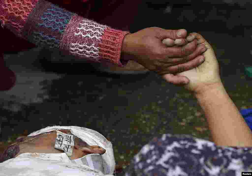 Женщина держит за руку погибшего при землетрясении родственника, Катманду, Непал