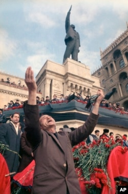 An unidentified man lifts his arms in grief under a statue of Lenin during a mass funeral in Baku on January 27, 1990.