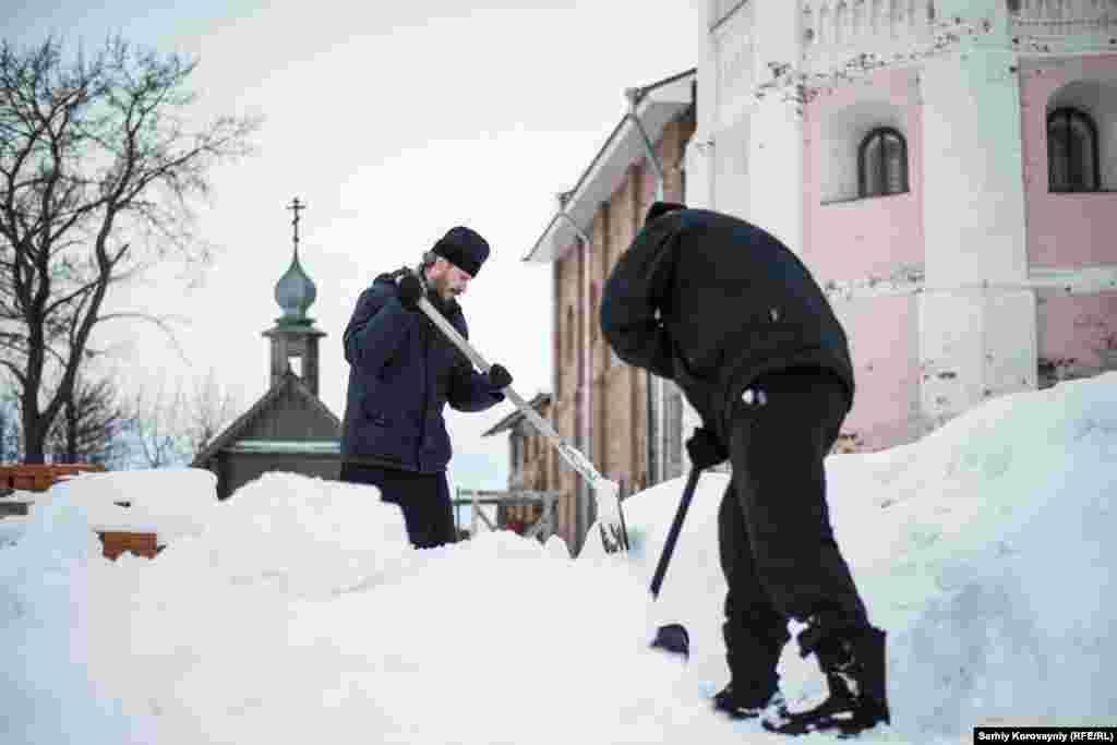 Настоятель монастыря Дионисий и прихожинин Кирилл убирают снег. Иногда Кирилл живет в монастыре неделями, участвует в религиозных церемониях и помогает с каждодневными делами