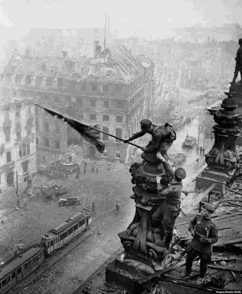 """На другой фотографии, снятой с того же места, видно, что солдата с флагом носит часы и на левой, и на правой руке. Это – доказательство мародерства, которое существовало и Красной армии. Халдей сказал, что его начальник в ТАСС вызвал его к себе и обратил внимание на эту деталь. """"Настоящий советский солдат не мародерствует … Быстро это исправь, убери с негатива"""", – сказал он. 28-летний фотограф сцарапал вторые наручные часы с пленки булавкой"""