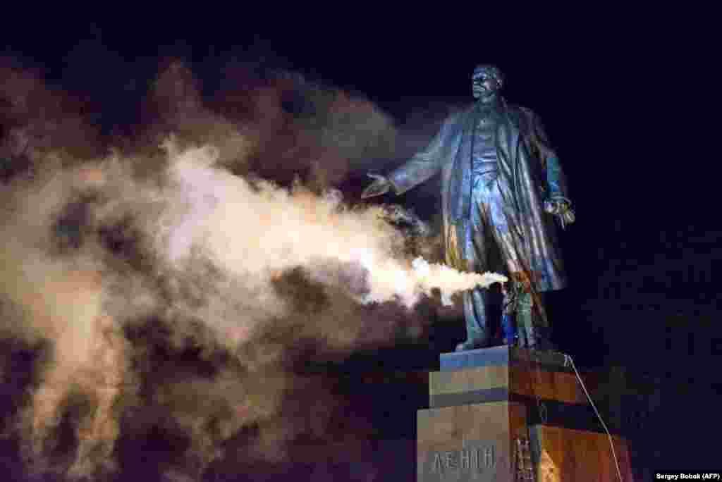 Активист с файером на постаменте памятника