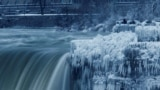 CANADA -- A lone visitor takes a picture near the brink of the ice covered Horseshoe Falls in Niagara Falls, Ontario, Canada, January 3, 2018.