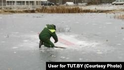 Сотрудник коммунальной службы вырубает бело-красно-белый флаг из-подо льда