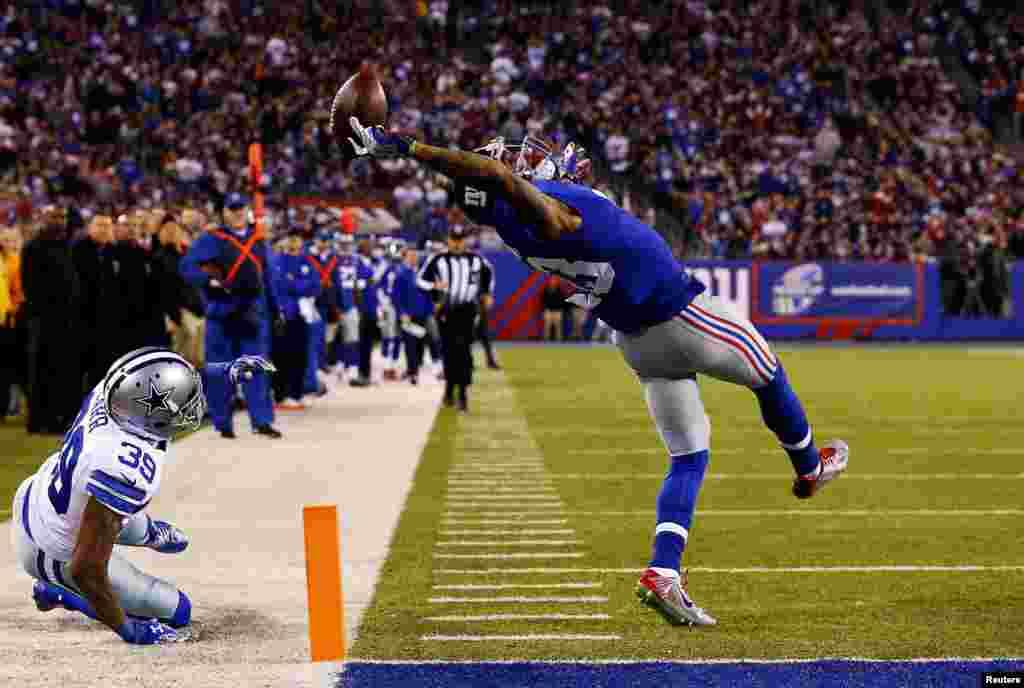 """Игрок клуба американской Национальной футбольной лиги New York Giants Оделл Бекхэм зарабатывает тачдаун в матче против Dallas Cowboys. Фотография Эла Белло, первое место в категории """"Спорт. Одиночные снимки""""."""