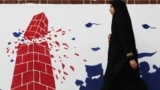 Tehran, Iran - A woman walks past an anti U.S. mural on the former U.S. Embassy's wall in Tehran, Iran January 7, 2020. Nazanin Tabatabaee/WANA (West Asia News Agency) via REUTERS
