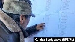 Избиратель в Караколе ищет свое имя в списках. 10 января 2021 года
