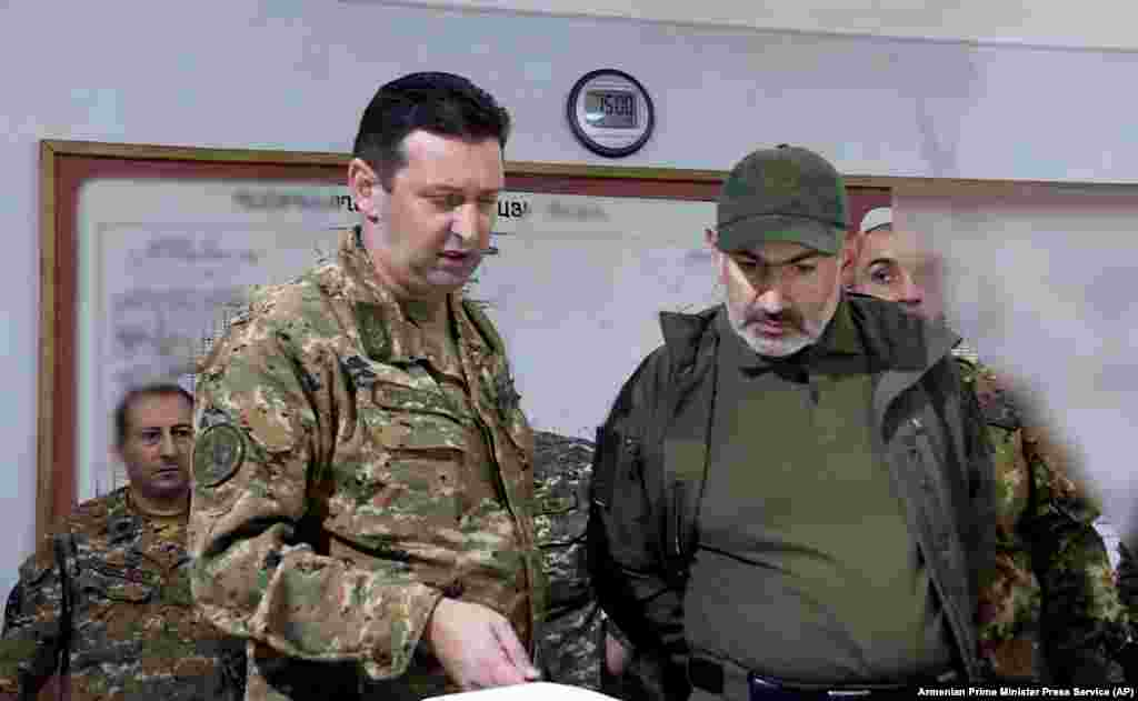 In this photo from the Armenian government, Armenian Prime Minister Nikol Pashinian, right, attends an October 6, 2020 meeting with army commanders in the breakaway Nagorno-Karabakh region. A teenager during the 1988-1994 Karabakh conflict with Azerbaijan, Pashinian, unlike his predecessor, former Prime Minister and President Serzh Sarkisian, a Karabakhi native and commander of the region's fighters during the initial conflict with Azerbaijan, has no firsthand military experience in the region.