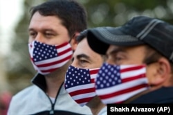 Supporters of the United National Movement, a strongly pro-U.S. party, wear face masks with the Georgian and U.S. flags at a campaign rally in Tbilisi on October 29, 2020.