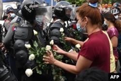 Протестующие вставляют цветы в щиты полицейских во время протестов в Янгоне 6 февраля