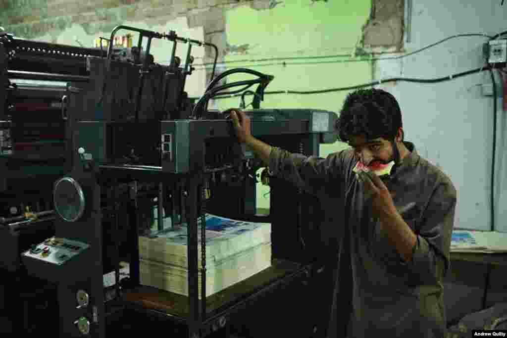На фото типограф ест арбуз, пока печатается газета