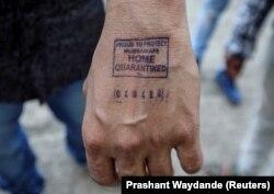 Мужчина показывает штамп с датой прибытия из-за границы, поставленный ему в аэропорту Мумбаи, Индия. 21 марта 2020 года. Фото: Reuters