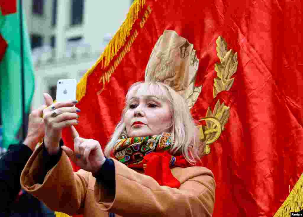 Женщина делает селфи на фоне красного флага в Минске. 7 ноября