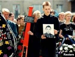 Мальчик держит портрет своего погибшего друга, 16-летнего Андрея Кулака, во время похоронной церемонии в Минске, 1 июня 1999 года