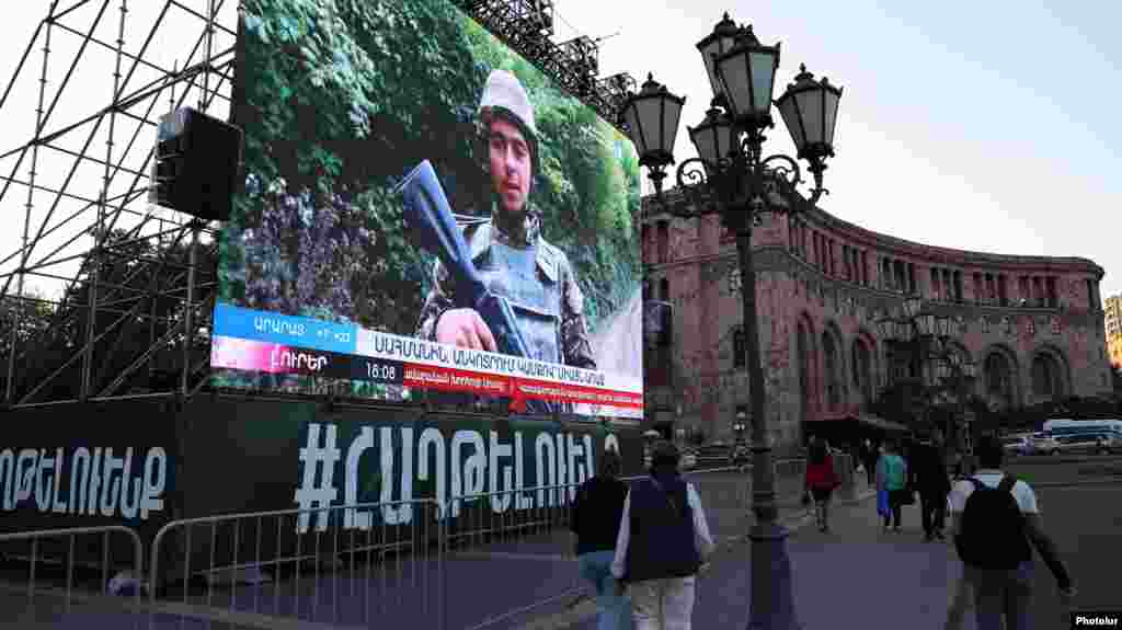 A screen placed on downtown Yerevan's Republic Square, not far from Armenian Prime Minister Nikol Pashinian's office, shows a state TV report on the war in Nagorno-Karabakh on October 9, 2020, as ceasefire talks began in Moscow. Although the Armenian government has not recognized its independence from Azerbaijan, Karabakh, predominantly inhabited by ethnic Armenians, is seen as an integral part of Armenia's heritage.