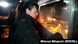 Мать Давида Драгичевича ставит свечу в память о сыне