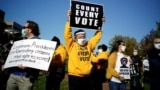 Pennsylvania, U.S. - People hold signs as they take part in a rally demanding a fair count of the votes of the 2020 U.S. presidential election, in Philadelphia
