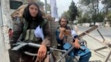 Members of Taliban forces sit at a checkpost in Kabul, Afghanistan