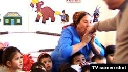 Воспитательница детского садика целует руку Бердымухамедова.