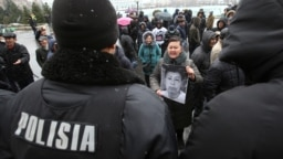 KAZAKHSTAN -- Participants stand in front of Kazakh police officers during a meeting in memory of anti-government activist Dulat Agadil, who recently died in a police detention center, in Almaty, February 27, 2020