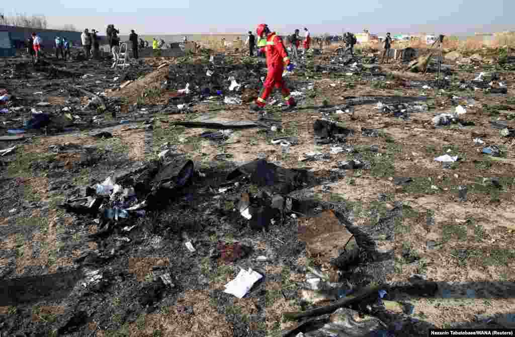 Член спасательной команды идет среди обломков самолета, принадлежащего Международным авиалиниям Украины, который был сбит иранскими военными после взлета из аэропорта Имама Хомейни на окраине Тегерана, Иран, 8 января 2020 года