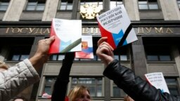 Russia -- Participants hold booklets containing the Constitution of the Russian Federation during a protest against a housing resettlement program outside the building of the State Duma, in central Moscow, June 14, 2017