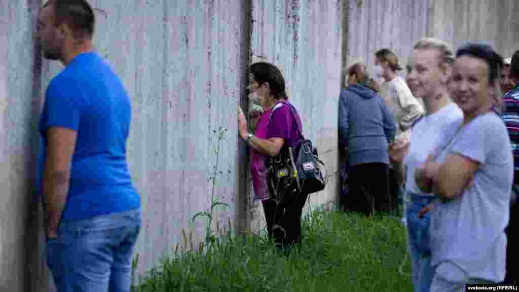 Люди, которые из-за большой очереди не смогли попасть на предвыборный пикет кандидата в президенты Светланы Тихановской в Слониме, наблюдают за ее выступлением через щели в ограждении футбольного стадиона. 1 августа.