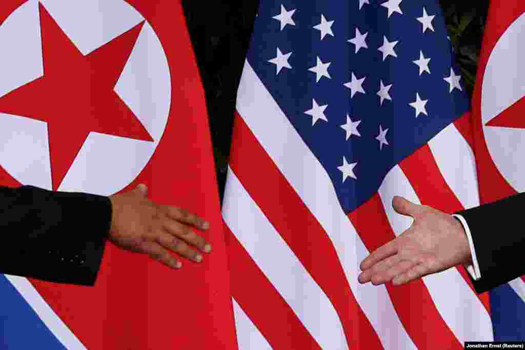 Лидер Северной Кореи Ким Чен Ын жмет руку президенту США Дональду Трампу во время американо-корейского саммита в Сингапуре