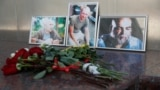 RUSSIA -- Photographs of journalists, (R-L) Orhan Dzhemal, Kirill Radchenko and Aleksandr Rastorguyev, who were recently killed in Central African Republic by unidentified assailants, are on display outside the Central House of Journalists in Moscow, Augu