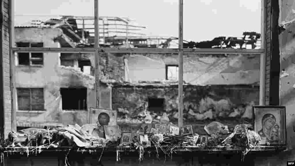 Иконы, цветы, бутылки с водой, еда и свечи на окнах спортзала. Школа №1, Беслан, Северная Осетия. 17 сентября 2004. Джеймс Хилл