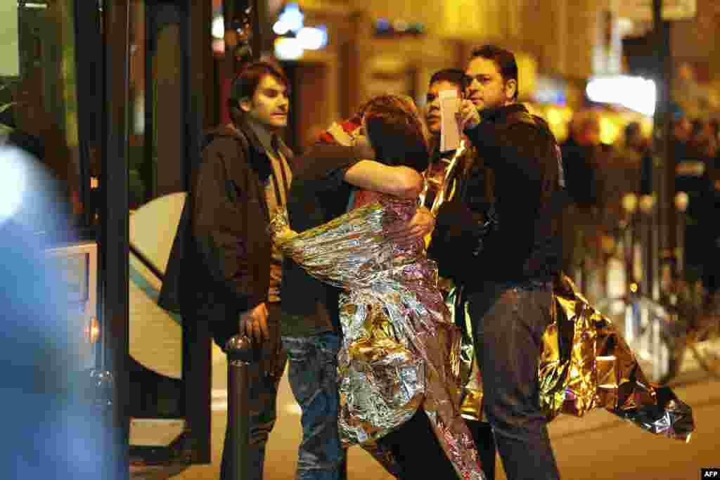"""Люди рядом с концертным залом """"Батлакан"""" обнимают друг друга после штурма"""
